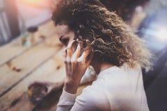 Усмехаясь милая молодая женщина делая переговор вызывает с ее друзьями через телефон клетки пока посылающ свободное время на горо стоковое фото