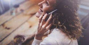 Усмехаясь милая молодая женщина делая переговор вызывает с ее друзьями через телефон клетки пока посылающ свободное время на горо стоковые изображения