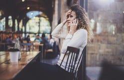 Усмехаясь милая молодая женщина делая переговор вызывает с ее друзьями через телефон клетки пока посылающ свободное время на горо стоковая фотография rf