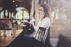 Усмехаясь милая молодая женщина делая переговор вызывает с ее друзьями через телефон клетки пока посылающ свободное время на горо стоковые изображения rf