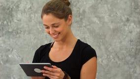 Усмехаясь милая молодая женщина используя таблетку в студии йоги Стоковые Изображения RF