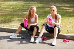 Усмехаясь милые девушки сидя с водой после тренировки на естественной предпосылке Расслабляющая концепция спорт Стоковое Изображение