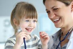 Усмехаясь милый маленький пациент взаимодействуя с женским доктором стоковое изображение
