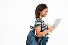 Усмехаясь милая африканская девушка студента с рюкзаком используя таблетку ПК Стоковые Изображения