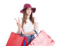 Усмехаясь милая девушка делая победу или знак мира на покупках Стоковые Фотографии RF