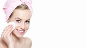 Усмехаясь милая девушка с совершенным цветом лица очищая ее сторону используя мягкую косметическую пусковую площадку хлопка стоковые изображения