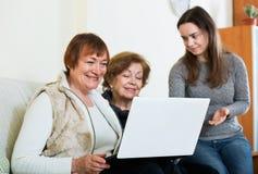 Усмехаясь милая девушка уча положительным старшим женщинам используя компьтер-книжку Стоковое фото RF