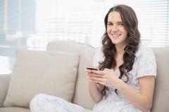 Усмехаясь милая женщина в pyjamas посылая текст стоковое изображение