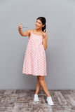 Усмехаясь милая женщина делая фото selfie на smartphone Стоковые Изображения