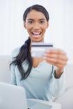 Усмехаясь милая женщина используя ее компьтер-книжку для того чтобы купить онлайн стоковые изображения