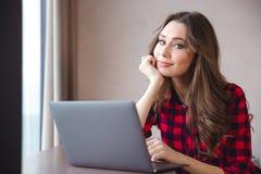 Усмехаясь милая женщина используя портативный компьютер Стоковое Изображение RF