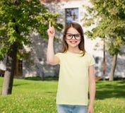 Усмехаясь милая маленькая девочка в черных eyeglasses Стоковое Фото