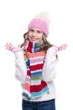 Усмехаясь милая маленькая девочка нося связанный свитер и красочный шарф, шляпу, mittens изолированные на белой предпосылке Одежд Стоковая Фотография