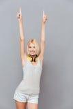 Усмехаясь милая молодая женщина указывая вверх с обеими руками Стоковые Изображения