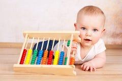 Усмехаясь милый малыш играя с абакусом Стоковое фото RF