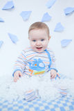 Усмехаясь милый младенец в питомнике играя с белизной вниз Стоковое фото RF