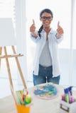 Усмехаясь милый художник давая большие пальцы руки до камеры стоковая фотография rf