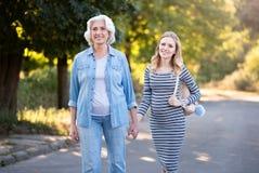 2 усмехаясь милых женщины идя в парк Стоковые Изображения