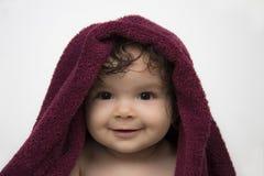 Усмехаясь младенец в красном полотенце ванны стоковые изображения