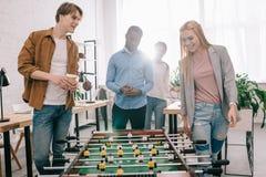 усмехаясь многонациональные предприниматели идя сыграть настольный футбол в современном стоковые фото