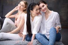Усмехаясь многонациональные девушки сидя на поле совместно Стоковые Фотографии RF