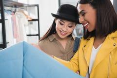 Усмехаясь многонациональные женщины выбирая одежды на магазине Стоковая Фотография