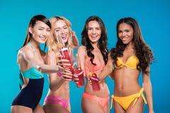 Усмехаясь многонациональные женщины в купальниках clinking с коктеилями Стоковое фото RF