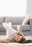 Усмехаясь мобильный телефон молодой женщины говоря пока кладущ на пол Стоковое Изображение