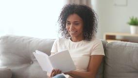 Усмехаясь молодая африканская женщина сидя на книге чтения софы сток-видео