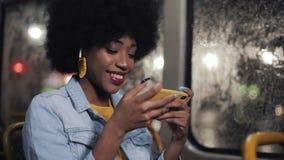 Усмехаясь молодая Афро-американская женщина наблюдая смешное видео на катании смартфона в общественном транспорте Nighttime видеоматериал