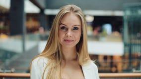 Усмехаясь молодая белокурая женщина смотрит очаровательную отладку ее волосы для камеры сток-видео
