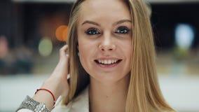 Усмехаясь молодая белокурая женщина смотрит очаровательную отладку ее волосы для камеры акции видеоматериалы