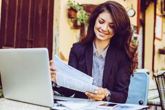 Усмехаясь молодая бизнес-леди смотря документы Стоковое Изображение