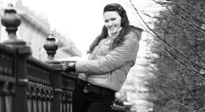 Усмехаясь молодая женщина в красной куртке осени на предпосылке города Стоковые Изображения RF