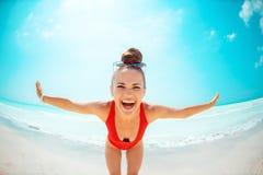 Усмехаясь молодая женщина в красном купальнике на пляже имея время потехи стоковое изображение