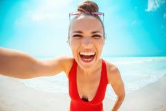 Усмехаясь молодая женщина в красном купальнике на seashore принимая selfie стоковое изображение rf