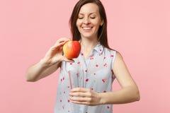 Усмехаясь молодая женщина в одеждах лета держа свежую зрелую красную чашку стекла плода яблока изолированный на розовой пастельно стоковое изображение