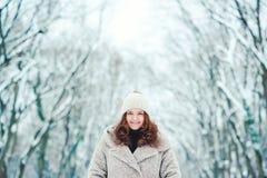 Усмехаясь молодая женщина в пальто идя на парк зимы Выражать девушку с положительными эмоциями, настроение рождества, изумляя улы стоковая фотография