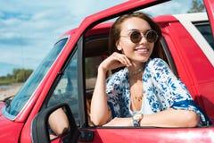 усмехаясь молодая женщина в солнечных очках в автомобиле стоковое фото rf