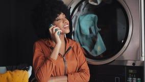 Усмехаясь молодая женщина говоря на мобильном телефоне на автоматической прачечной акции видеоматериалы