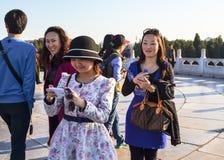 Усмехаясь молодая женщина делая фото используя smartphones Стоковые Изображения RF