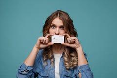 Усмехаясь молодая женщина держа кредитную карточку золота Изолированный портрет стоковая фотография