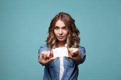 Усмехаясь молодая женщина держа кредитную карточку золота Изолированный портрет стоковые изображения rf