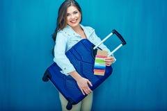 Усмехаясь молодая женщина держа чемодан, пасспорт, билет стоковая фотография rf