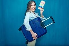 Усмехаясь молодая женщина держа чемодан, пасспорт, билет стоковое фото rf