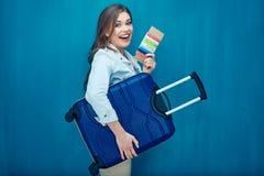Усмехаясь молодая женщина держа чемодан, пасспорт, билет стоковые фото