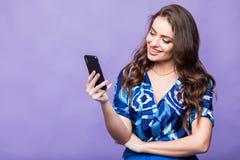 Усмехаясь молодая женщина думая и используя телефон на фиолетовой предпосылке стоковые изображения rf