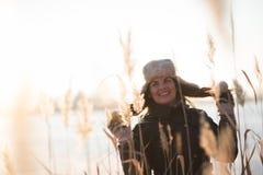 Усмехаясь молодая женщина зимы смотря прочь стоковое изображение