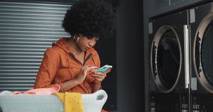 Усмехаясь молодая женщина используя смартфон на автоматической прачечной Прачечная самообслуживания общественная видеоматериал