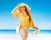 Усмехаясь молодая женщина на seashore держа тапочки лета стоковая фотография